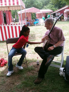 Storyteller with banjo talking with young girl.